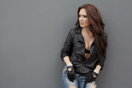Young woman in jeans and leather jacket near gray wall photo