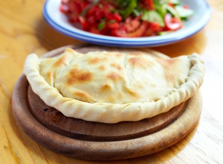 Close-up closed italian pizza calzone on the wood table Stock Photo
