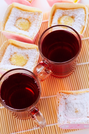 Close up cup of tea and cupcake on background photo