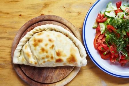 Close-up closed italian pizza calzone on the wood table 版權商用圖片