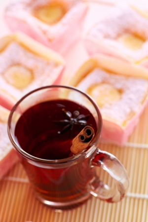 Close up cup of tea with cinnamon and cupcake  photo