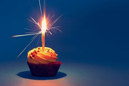 Cupcakes met kaars en room op de blauwe Stockfoto
