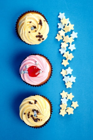 birthday cupcakes: Cupcakes with candle and cream on the blue  Stock Photo