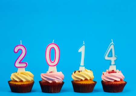 Cupcakes with candles 2014 on the colored background