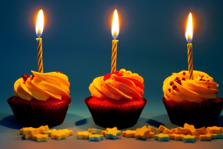 Cupcakes with candle and cream on the blue background photo