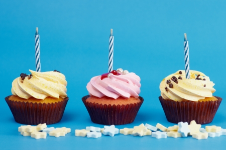 birthday cupcakes: Cupcakes with candle and cream on the blue background