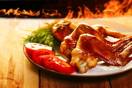 bbq background: Chicken wings BBQ with vegetables on the plate, and fire on background