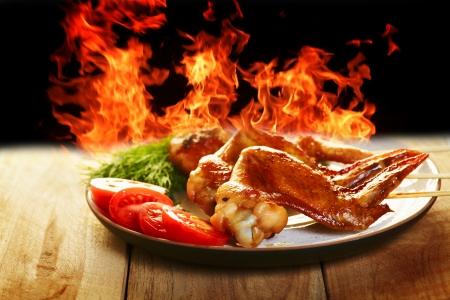 접시에 야채와 함께 닭 날개 BBQ 및 배경에 화재