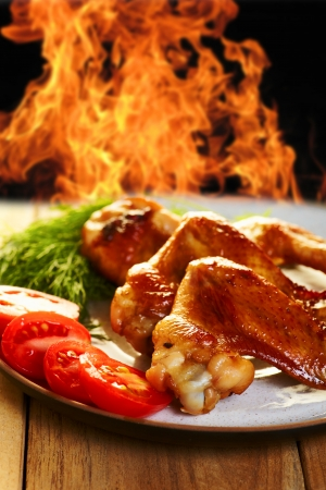 Chicken wings BBQ with vegetables on the plate, and fire on background photo