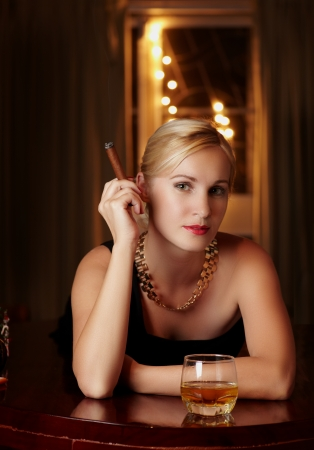smocking: Blonde woman in black dress with glass whisky against lights