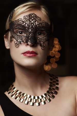Portrait blond woman in mask against dark photo
