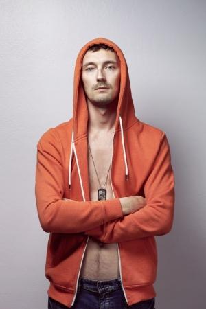 Brutal man in red jacket with hood in studio 版權商用圖片