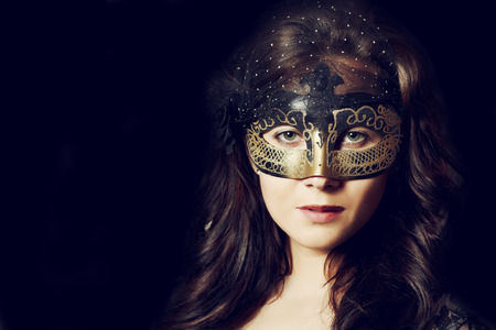 Young brunet woman in dark mask and dress in studio fashion style photo