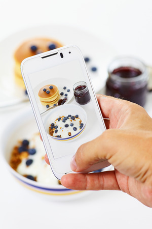 Close up eropean brreakfast outmeal waffer and jam on the white, and mobile phone in hand Stock Photo - 31250779