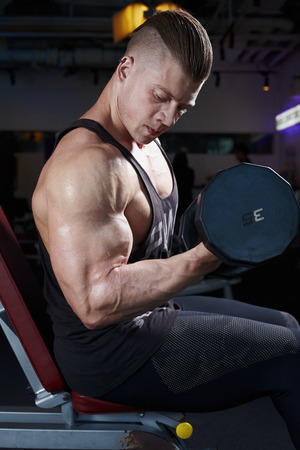 brawny: Athletic bodybuilding man in gym working with gantels Stock Photo