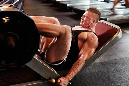 Athletic bodybuilding man in gym leg lifting weight 版權商用圖片