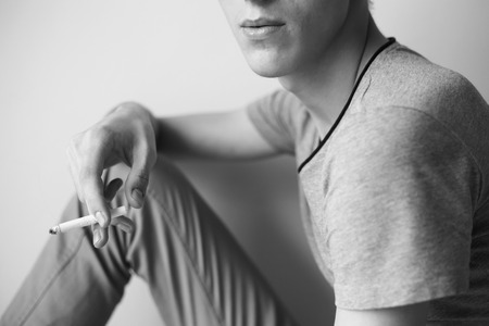 Close up cigarette in young guy hand in black and white photo