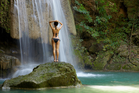 Female model in bikini in nature waterfall in Erawan, Thailand