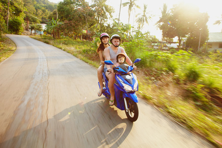 Young family on the motorcicle on the asia travel road in morning sunlight photo