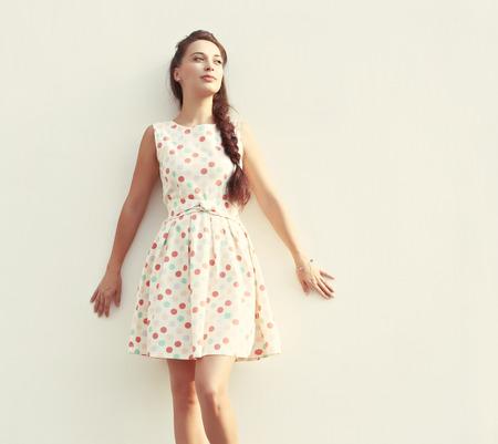 흰색 벽에 여름 드레스에 세로 젊은 모델
