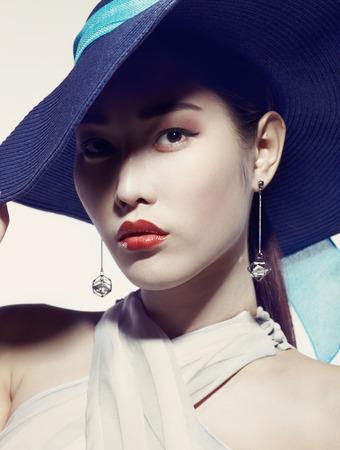 Aziatische mannequin in hoed tegen witte achtergrond