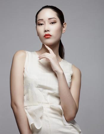 Aziatisch vrouwelijk schoonheidsmodel in studio tegen grijze achtergrond Stockfoto