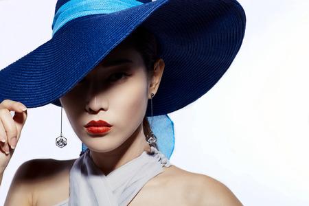 donne eleganti: Modella asiatico in cappello su sfondo bianco