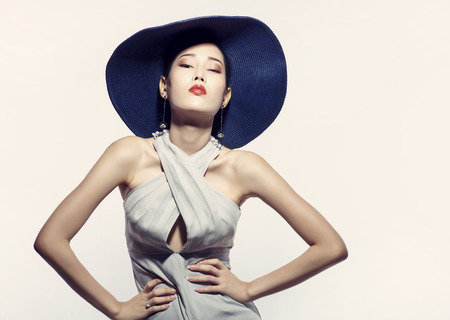 Asian fashion model in hat against white background