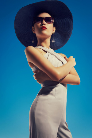glamour model: Asian fashion model in sunglasses and hat against bluse sky background Stock Photo