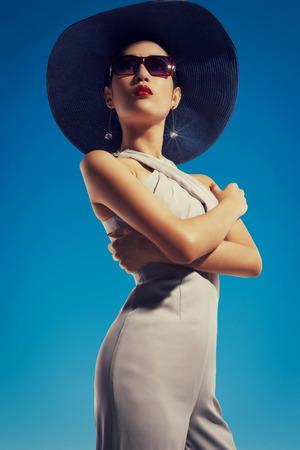 Aziatische fashion model in zonnebril en hoed tegen bluse hemel achtergrond Stockfoto