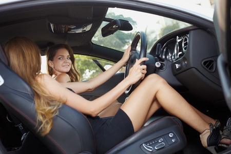 Young girl in dress in luxury motor car photo