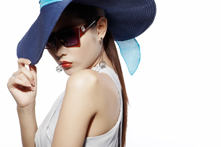 Asian fashion model in sunglasses and hat against white background Stock Photo