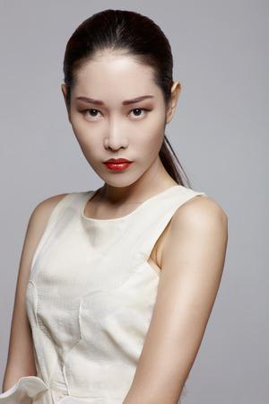 Aziatische vrouwelijke schoonheid model in de studio tegen grijze achtergrond