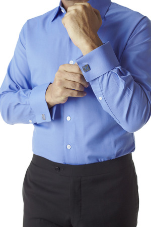 cuffs: Closa up man torso in blue shirt with cufflinks in cuffs against white