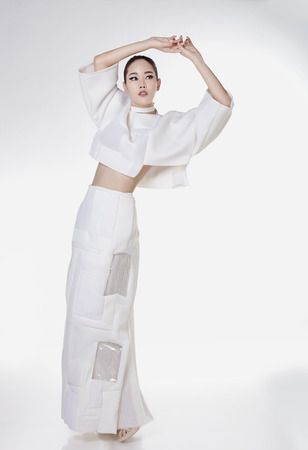 Asian fashion model in white dress in studio against white background