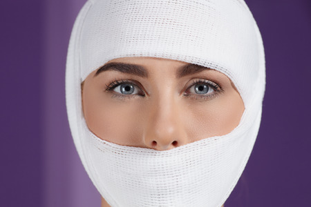 plastic glove: Close up models face in medical bandage after bueauty surgery Stock Photo