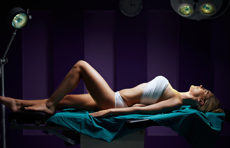 breast beauty: woman in dark surgery room lieing on surgical table under light for bueauty surgery Stock Photo