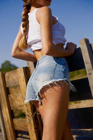 cowgirls: chica sexy en pantalones cortos de mezclilla otside en el pueblo bajo la luz solar por la noche