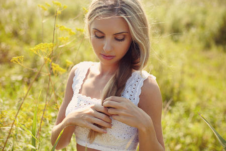 fun activity: Outside portrait young woman in white dress in outside in the meadow under sunlight