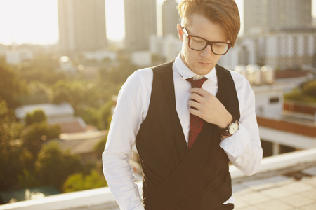 vogue style: Young man in casual fashion hipster stylein glasses, and cityline on background Stock Photo