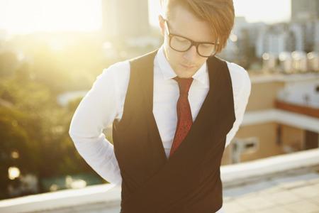 Jonge man in casual mode hipster stylein glazen en cityline op de achtergrond Stockfoto