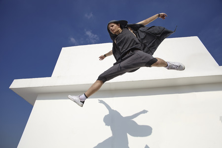 trendy male: Fashion and sporty young guy in jumping against white wall and blue sky