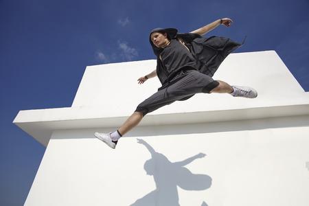 poses de modelos: Moda y chico joven deportivo en el salto contra la pared blanca y el cielo azul