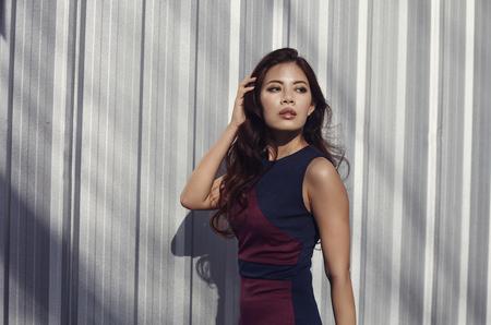 poses de modelos: modelo de mujer asiática en el vestido, y con el pelo largo en el aire libre en la calle
