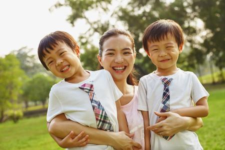 Aziatische familie moeder en twee tweelingen jongens in het park