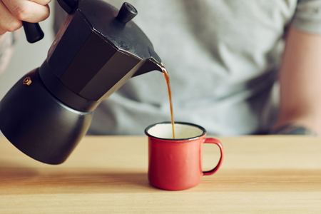 Coffee maker and cup from metal with coffee and men torso behind 版權商用圖片