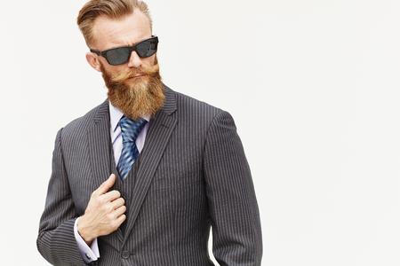 Handsom baard mannelijke model in pak en een zonnebril tegen een witte achtergrond