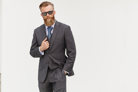 man style: Handsom beard male model in suit and sunglasses against white background
