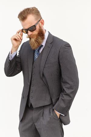 Handsom baard mannelijk model in pak en zonnebril tegen witte achtergrond