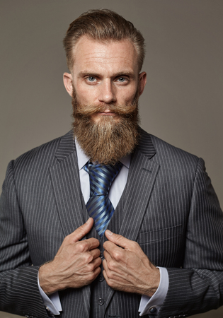 brutal man with beard in classic suit in modern style portrait Stock Photo